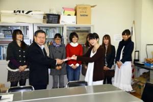集まったお金を国際地域文化専攻1年代表の中島さんから贈呈される池田会長